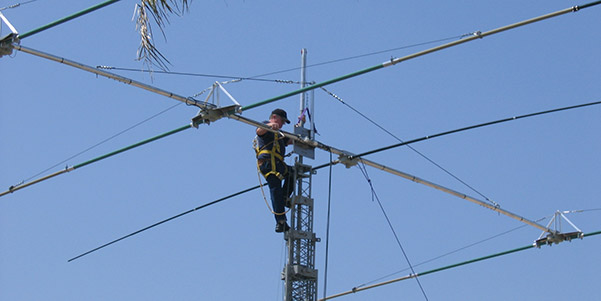 Image of a service operator atop an antenna making adjustments